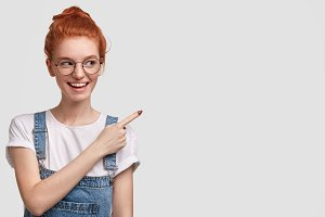 Horizontal shot of happy female student with pleasant smile, being glad to advertise something, points at blank copy space for your promotional text or advertisement. Ginger youngster gestures