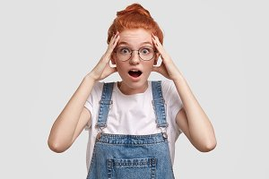 Stunned teenage girl with red hair, forgets about something important, stares at camera with jaw dropped, wears denim stylish overalls, shocked to hear awful news from interlocutor, poses alone