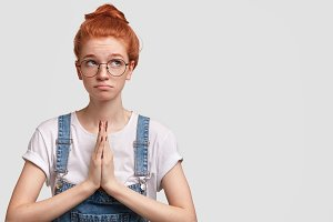 Attractive sorrowful female with ginger hair bun, presses palms together in gesture of pray, begs for something she needs, has miserable look upwards, isolated on white background, space for your text