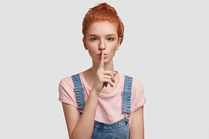 Portrait of serious red haired female with freckled skin, keeps fore finger on lips, shows hush sign, poses against white background, asks to be quiet. European ginger woman gestures in studio