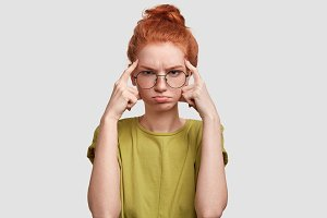 Unhappy thoughtful female with freckled skin, keeps fore fingers on temples, curves lips, has disappointed expression, poses against white background. Ginger young woman finds solution in mind