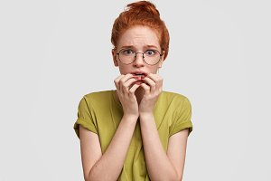 Impressed nervous female with ginger hair, feels stressed and embarrassed as finds out bad unexpected news, wears bright green t shirt, isolated over white concrete wall. Stunned red haired woman