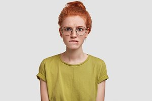 Photo of adorable freckled ginger young female bites lower lip and looks in bewilderment, wears casual t shirt, poses against white studio background, wears casual green t shirt and spectacles