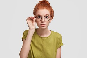 Portrait of attentive female college student with foxy hair, looks scrupulously through round spectacles, sees something strange or unexpected, poses against white background. Wow, what I see!