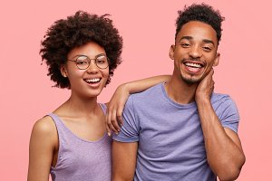 Positive African American couple have fun together, smile positively, embrace and support each other, pose together against pink background. Joyful dark skinned woman and her best dark skinned friend