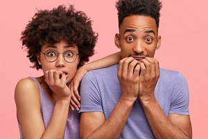 Close up shot of worried African American male and female students, waits for announcement of exam results, bite finger nails, stare at camera, pose together against pink background. Friendship