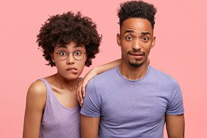Photo of puzzled African couple stare at camera, bite lower lips as being surprised to see something in front. Beautiful female with Afro hairstyle leans at friend`s shoulder, pose together in studio