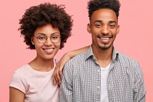 Ethnicity, friendship, relationship concept. Photo of delighted female with Afro hairstyle, has broad smile, leans at friend`s shoulder, spend free time together. Young African American family couple