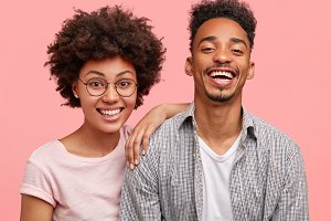 Positive dark skinned guy has date with girlfriend, have fun together, pose at camera with broad smiles, pose together against pink background. African American woman has curly hair and her friend