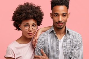 Cropped shot of lovely African American couple, embrace, stand close to each other: beautiful female in round eyewear leans at husband, enjoy free time together, have good relationship, understanding