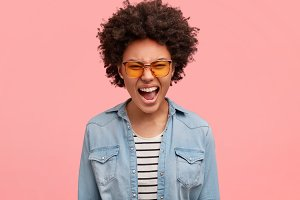 Annoyed frustrated dark skinned woman exclaims with anger, expresses negative emotions, wears fashionable yellow sunglasses and denim jacket, poses against pink background. It is outrageous!