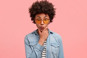 Hesitant African American female holds chin and curves lips with uncertainty, feels puzzled while makes choice, poses against pink studio background. Puzzled dark skinned mixed race woman hipster