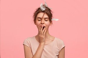 Sleepy female yawns as being tired and needs good rest after hard working day, has feather on head, gets up early in morning, isolated on pink wall. It`s already bed time. Rest and sleeping concept