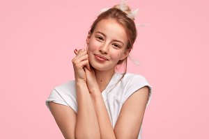 Lovely young female with gentle smile, healthy skin, has no make up, wakes up in morning, looks at mirror with delighted expression, isolated over pink background. It`s high time for rest and sleep!