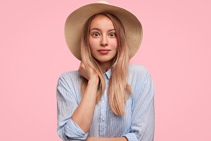 Adorable stunned female wears straw hat and striped casual shirt, being shocked to hear weather forecast, was going to spend day on beach, isolated over pink background. Young woman looks in disbeleif