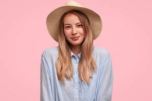 Horizontal portrait of beautiful female student glad to have vacations abroad, wears summer hat, going to have excursion across city, isolated over pink background. Gorgeous young businesswoman