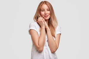 Portrait of delighted young Caucasian female with positive expression, keeps hands together, has gentle smile, being glad to hear good news, poses against white concete wall in casual clothing
