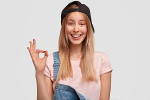 Cheerful positive female student or hipster girl, shows ok sign, being satisfied with something, has stylish clothes, smiles broadly, isolated over white background. Fashionable youngster in overalls