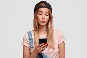 Cute teenager girl with nice appearance, wears stylish denim overalls and cap, holds modern cell phone, looks with hesitation into screen, recieves message from stranger, types answer or feedback