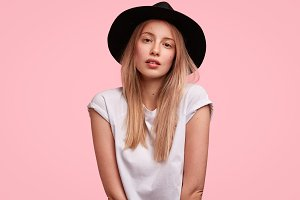 Beautiful fashion model in stylish summer hat, poses at camera with confident look, poses against pink studio background, likes to be photographed. Lovely young female spends leisure time alone