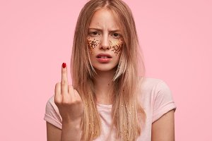 Annoyed female shows fuck sign, has argument with friend, looks with displeased expression at camera, isolated on pink studio background. Beautiful irritated young woman shows middle finger.