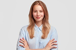 Cute intelligent female student looks confidently with satisfied expression, being glad to finish writing diploma paper, keeps arms folded, isolated on white background. Lovely woman in elegant shirt