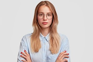 Studio shot of beautiful female youngster looks seriously at camera, listens attentively somebody, keeps hands crossed, wears big spectacles and striped shirt, poses against white concrete wall
