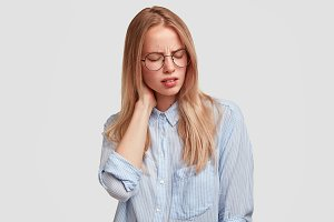 Tired female office worker in spectacles has pain in neck as sat long time in front of computer and prepared report, looks fatigue and exhausted, suffers from ache, isolated on white background.
