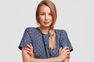 Image of European female has serious look and hands crossed, wears polka dot blouse, has plait, prepares for date with boyfriend, isolaed on white background. Young woman with confident expression