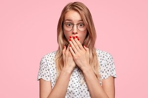 Shocked beautiful woman recieves unexepcted news from interlocutor, feels surprised, gossip together, wears spectacles and elegant blouse, isolated on pink background. Human reaction concept.