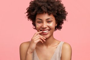 Close up shot of attractive young female wtith positive gentle smile, glad to have pleasant conversation with handsome guy, feels shy, isolated over pink background. Happy African American woman
