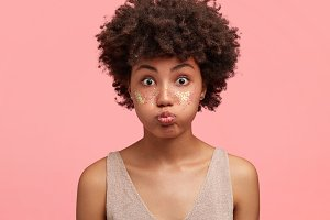 Funny amazed attractive African American female blows cheeks, has bated breath, cheeks decorated with spangles, stares at camera, prepared for party with friends, isolated over pink background