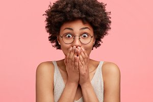 Studio shot of good looking surprised female model looks amazed, being shocked and happy to meet with former classmate after long time, has Afro haircut, poses against pink studio background