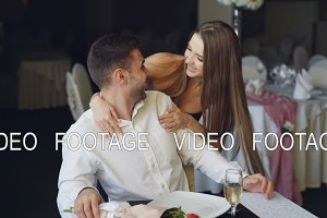 Pretty young woman is greeting her boyfriend in restaurant closing his eyes with her hands, hugging and kissing him, then taking flowers and sitting at table in front of him.