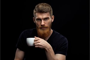 Perfect hairstyle bearded man drinking espresso