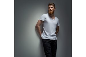 Portrait of a handsome man in a white t-shirt from the gray