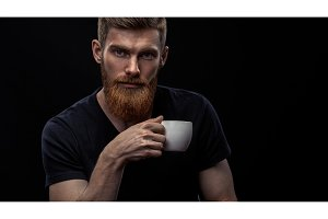 Bearded young man drinking espresso