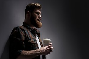 Side view of young bearded man drinking morning coffee