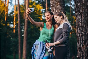 Two young sportive girlfriends wearing sportswear leaning against tree taking selfie with smartphone in forest