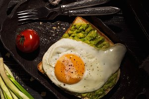 Sandwich with avocado and fried egg. Fresh breakfast in a rustic style. View from above.