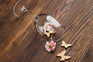 Wineglass with different decorations, wooden background