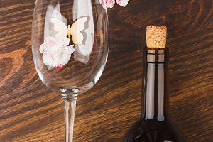Wineglass and bottle of wine with different decorations, wooden background