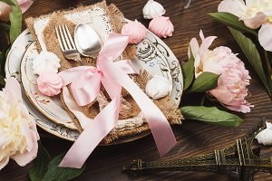 Tableware and silverware with peonies, decorations and meringues
