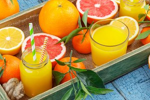 Different fruits and glass with fresh orange juice, wooden background