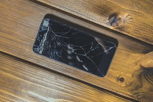 close up shot of a crashed mobile phone on a wooden surface