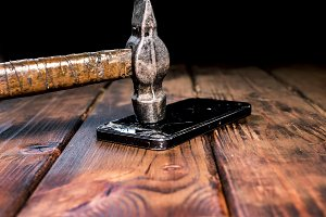 close up a hammer crashing a phone on a wooden surface