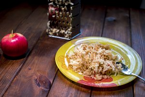close up plate with grated apple fruit in it on a wooden surface