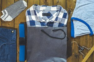 new men casual clothes and accessories on a wooden surface with a shopping bag