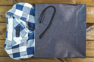 new checkered shirt pop out from shopping bag on a wooden background
