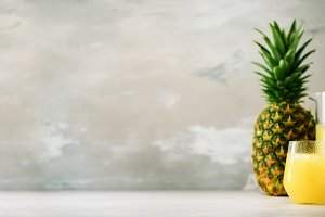 Pineapple juice in glassware and whole pineapple fruit on gray background. Copy space, sunlight effect. Summer, holiday concept. Raw, vegan, vegetarian, clean eating diet. Banner